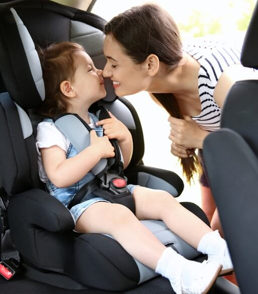 child in booster seat with 5 point harness