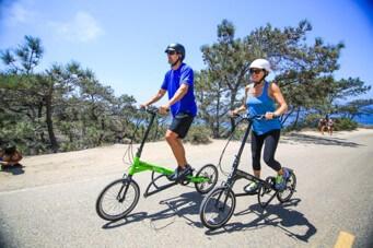 Man and Woman Riding ElliptiGO Arc 8 Elliptical Bikes on Road