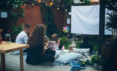 family watching outdoor projector