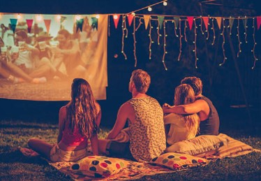 friends watching backyard movie on outdoor projector