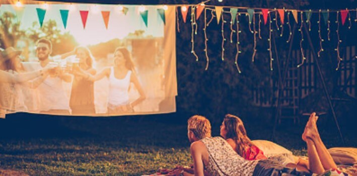 couple watching a ortable projector outside