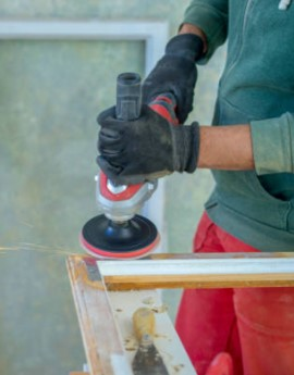 man using sander to remove paint from wood door frame