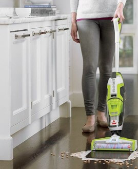 woman cleaning hardwood floors with wet dry vacuum
