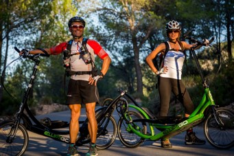 Man and Woman Riding ElliptiGO 8C Elliptical Bikes on Road